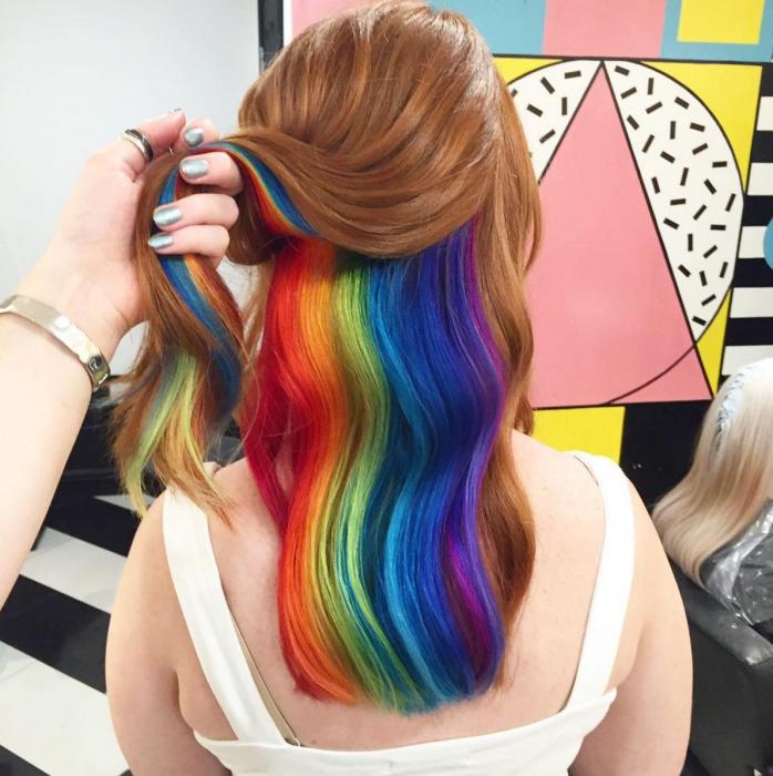 Chica con cabello largo color castaño rojizo con colores fantasía escondidos, rojo, anaranjado, amarillo, verde, azul, morado
