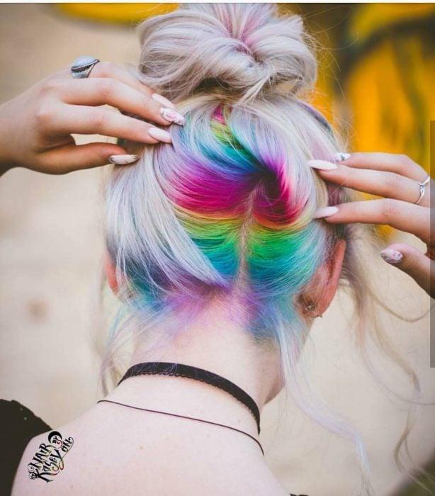 Mujer con manicure de flores, cabello gris con raíces pintadas de colores morado, azul, verde, amarillo y rosa