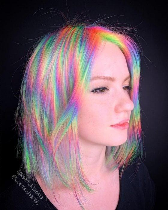 Chica con cabello corto y lacio, teñido de colores fantasía simulando el reflejo de la luz, verde, anaranjado, rosa, morado y amarillo