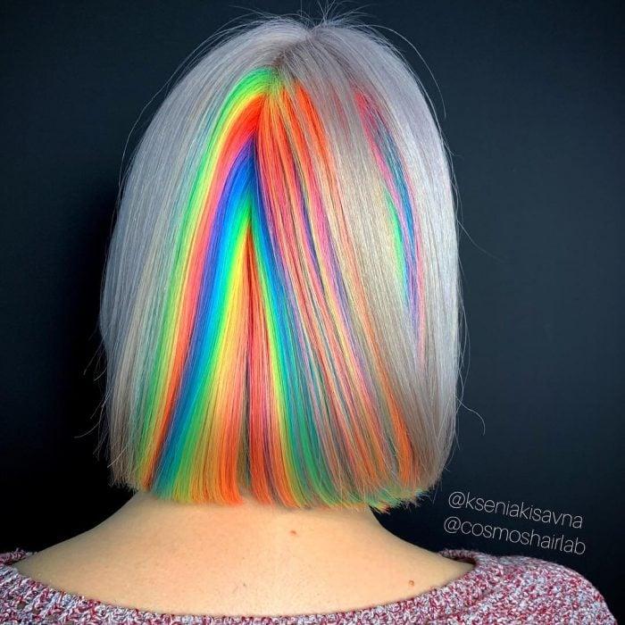 Chica con cabello corto y lacio, teñido de colores fantasía simulando el reflejo de la luz, verde, anaranjado, azul y amarillo