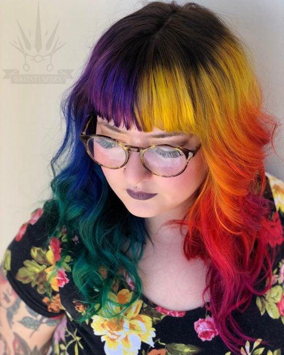 Chica de lentes retro con perforaciones en la nariz y vestido de flores, con cabello largo, ondulado y flequillo de colores del arcoíris, rosa, morado, azul, anaranjado, rojo, amarillo y verde