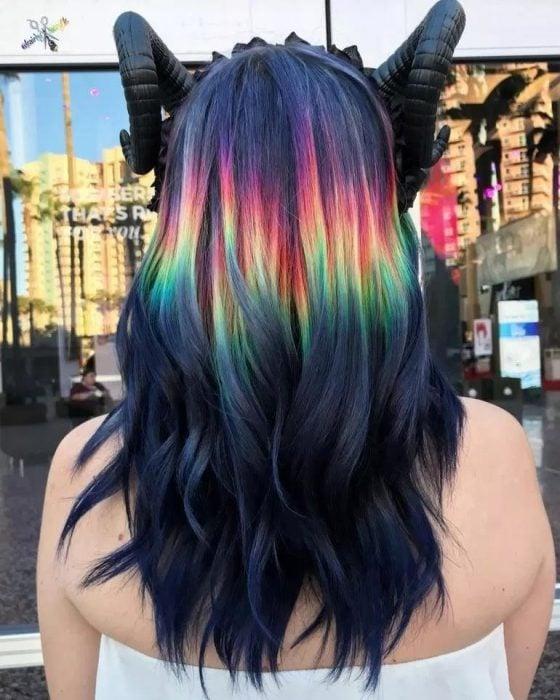 Chica con diadema de cuernos, cabello largo, ondulado, negro con una franda de colores arcoíris, morado, rojo, anaranjado, amarillo y verde