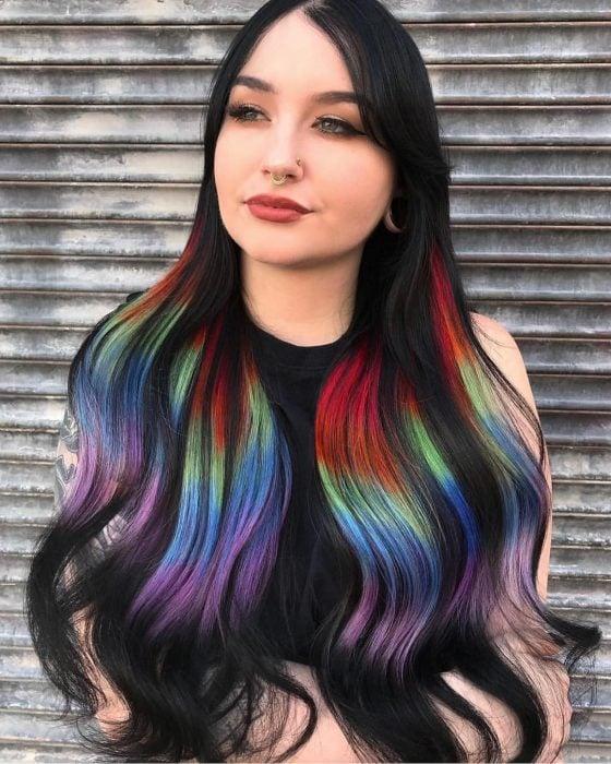 Chica con perforaciones en el septum y expansiones en las orejas con cabello largo color negro con partes rojas, anaranjadas, verdes, azules y moradas