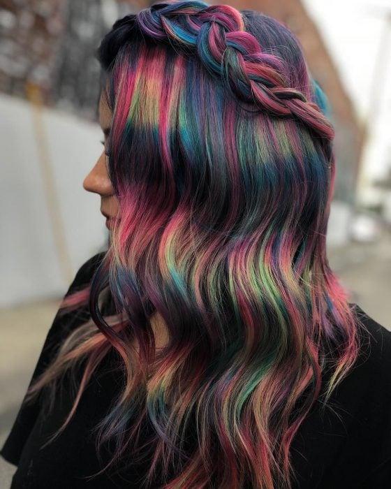 Chica de perfil con cabello ondulado peinado con una trenza y colores de fantasía oscuros, rosa, verde, azul y morado