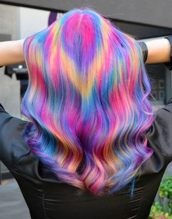 Chica con cabello largo pintado con colores de fantasía que parecen destellos de luz, rosa, azul, morado y amarillo