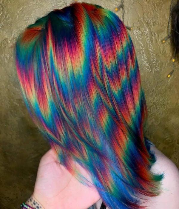 Mujer con cabello corto pintado con colores de fantasía que parecen destellos de luz, rosa, anaranjado, amarillo, verde y azul