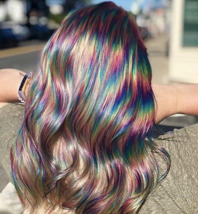 Mujer con cabello castaño rubio, ondulado con destellos de colores del aroíris, morado, rosa, amarillo, verde y azul