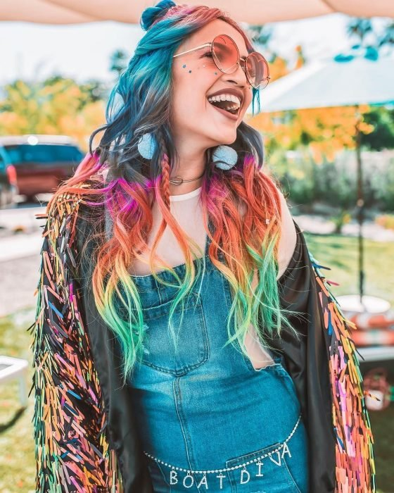Chica con estilo hippie, overol de mezclilla, lentes rosas redondos, lentejuelas de estrellas en la cara simulando pecas, cabello largo ondulado de colores del arcoíris, azul, rosa, anaranjado, amarillo y verde, y aretes felpudos azules