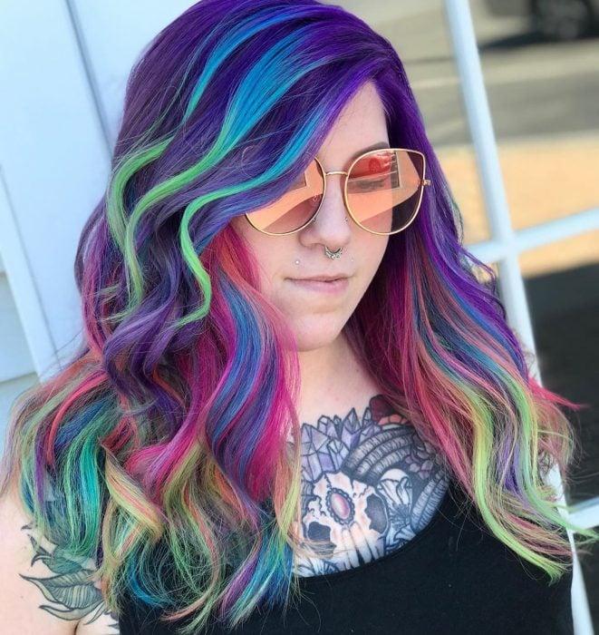 Chica con tatuaje en el pecho y perforaciones en la nariz y en el labio, con lentes rosas retro y cabello ondulado, largo y de colores del arcoíris, morado, azul, verde y rosa