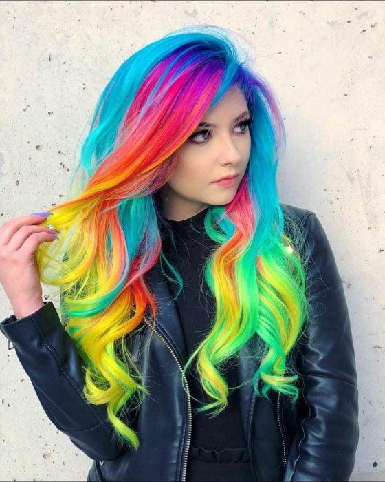 Chica de cabello largo, ondulado y de colores neón del arcoíris, rosa, morado, azul, anaranjado, rojo, amarillo y verde