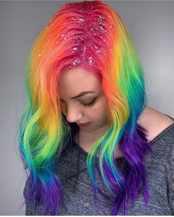 Chica con cabello largo, ondulado y de colores del arcoíris, rosa, anaranjado, amarillo, verde, azul y morado con diamantina en la raíz