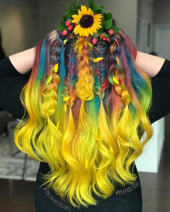 Chica con cabello largo y ondulado con trenzas, de colores del arcoíris, amarillo, verde, azul, anaranjado y morado, con una corona de girasol