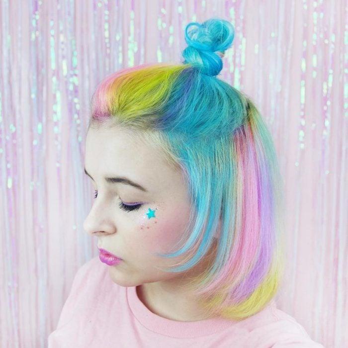 Chica con los ojos cerrados y una estrella en el pómulo, con cabello corto y lacio teñido de colores pastel, azul, rosa, amarillo y lila