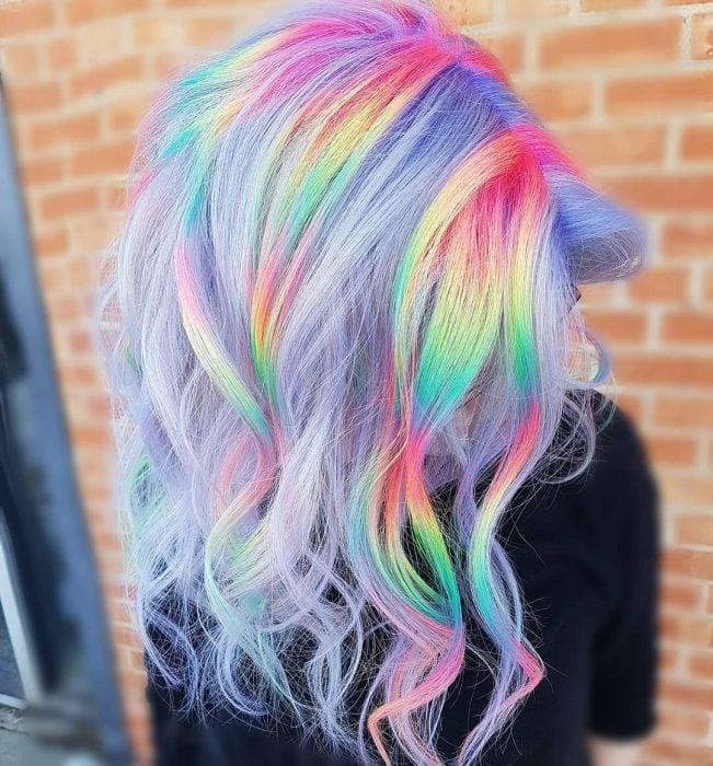 Chica con cabello largo y ondulado de colores lila con reflejos amarillos, verdes, azules y rosas