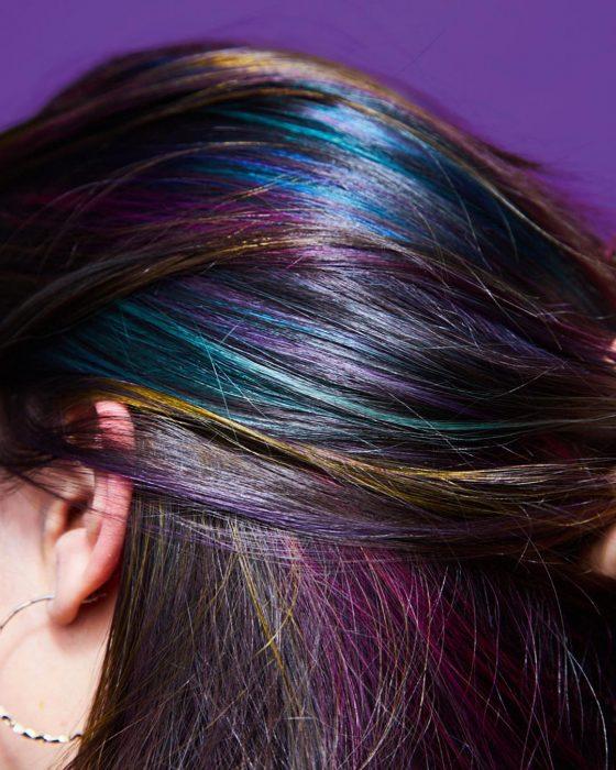 Tendencia de cabello, tinte oil slick que parece aceite derramado en el suelo, chica con reflejos de color azul, verde, amarillo, rosa y morado
