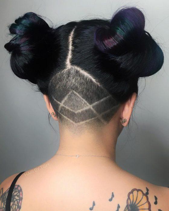 Tendencia de cabello, tinte oil slick que parece aceite derramado en el suelo, chica con cabeza rapada de atrás con figuras geométricas, con dos chongos altos, cabello color negro con reflejos morados y verdes