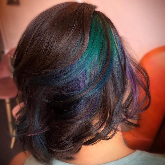 Tendencia de cabello, tinte oil slick que parece aceite derramado en el suelo, chica con la mitad del cabello pintado de colores morado, azul y verde