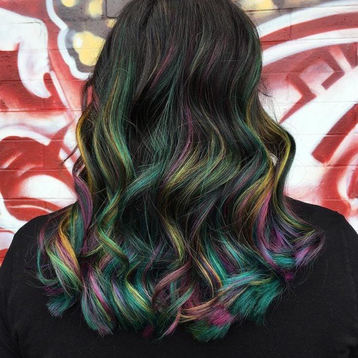 Tendencia de cabello, tinte oil slick que parece aceite derramado en el suelo, chica de cabello largo y ondulado de colores amarillo, verde, rosa, morado y azul