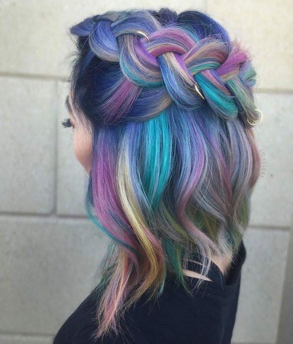 Tendencia de cabello, tinte oil slick que parece aceite derramado en el suelo, chica con peinado de trenza ancha con argollas, cabellera de colores lila, rosa, verde aqua y amarillo