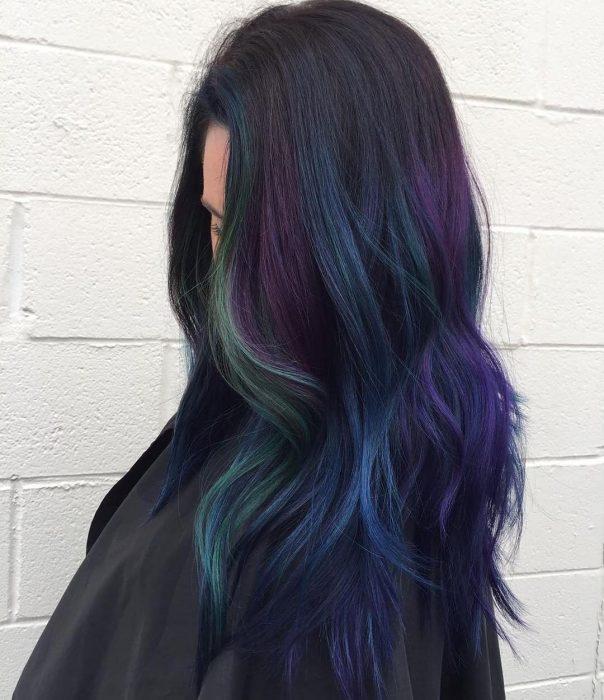 Tendencia de cabello, tinte oil slick que parece aceite derramado en el suelo, chica de cabello oscuro y largo con tonalidades verde, morado y azul