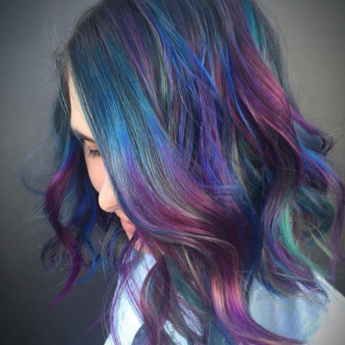Tendencia de cabello, tinte oil slick que parece aceite derramado en el suelo, chica con cabello corto, ondulado y de color azul morado, verde, rosa y amarillo