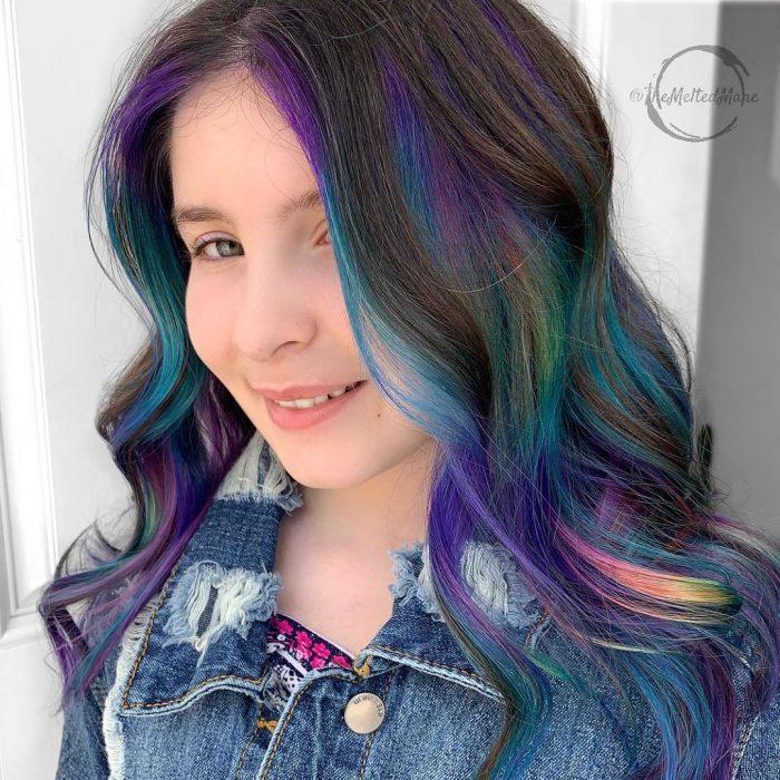 Tendencia de cabello, tinte oil slick que parece aceite derramado en el suelo, chica sonriendo con cabello largo, ondulado y de colores morado, azul, verde, rosa y amarillo