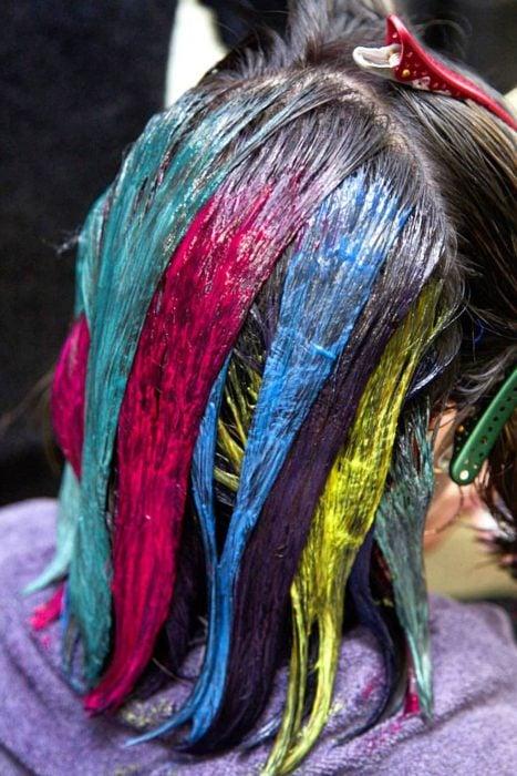 Tendencia de cabello, tinte oil slick que parece aceite derramado en el suelo, chica aplicándose tinte de colores rosa, azul, amarillo y verde