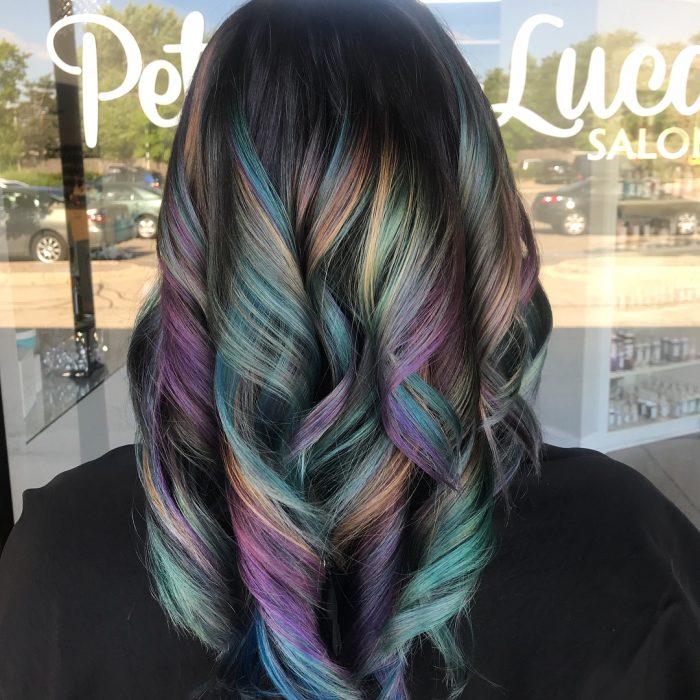 Tendencia de cabello, tinte oil slick que parece aceite derramado en el suelo, mujer con cabello de indas grandes, de color morado, verde, azul y anaranjado