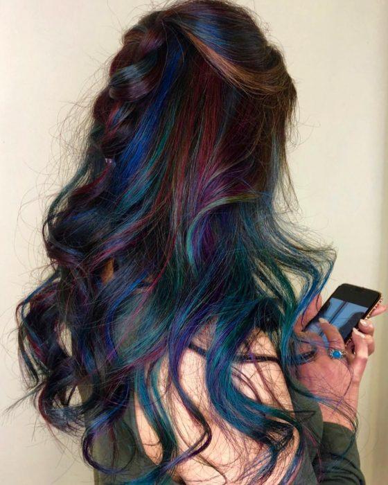 Tendencia de cabello, tinte oil slick que parece aceite derramado en el suelo, chica revisando su celular con cabello largo, ondulado peinado con una media trenza, de colores azul, morado, verde rosa y anaranjado