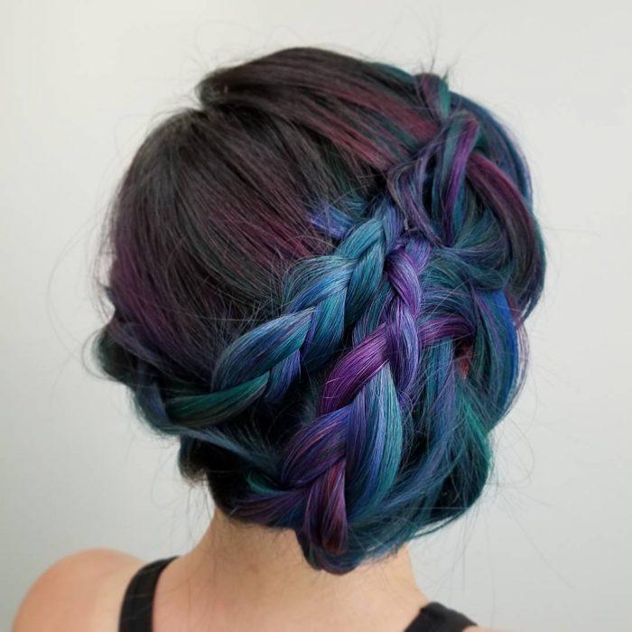 Tendencia de cabello, tinte oil slick que parece aceite derramado en el suelo, chica con peinado de trenza recogido, cabellera de colores morado, castaño y azul