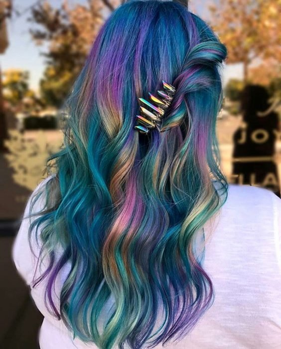 Tendencia de cabello, tinte oil slick que parece aceite derramado en el suelo, chica con cabello largo y ondulado de colores azul, morado, verde, rosa y anaranjado, con un broche tornasol