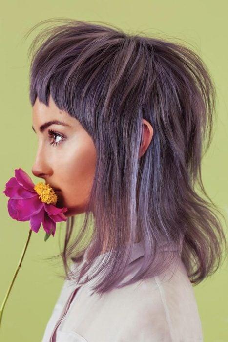 Chica de perfil oliendo una flor rosa con centro amarillo, cabello en capas hasta los hombros color gris lavanda o lavender gray