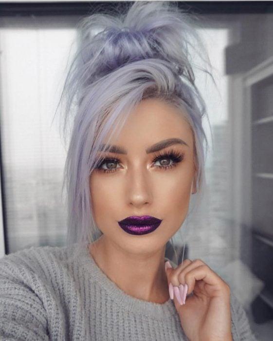 Mujer con pestañas postizas y labial color morado metálido, con cabello color gris lavanda o lavender gray con un chongo alto despeinado