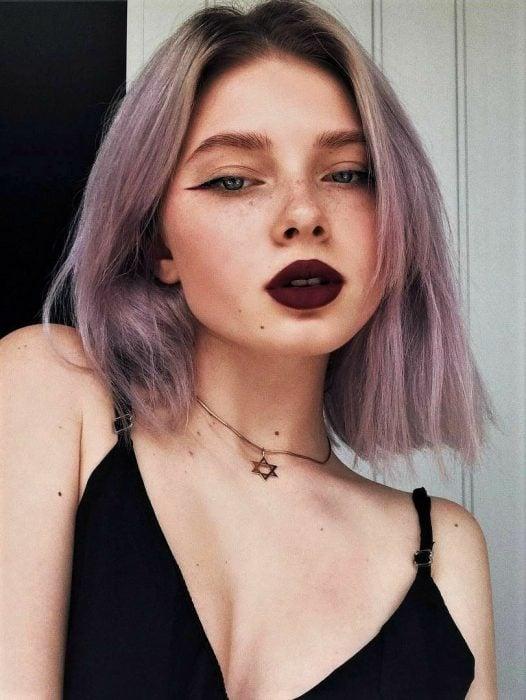 Chica indie con pecas, delineado cat eye, labal rojo vino y cabello corto y lacio color gris lavanda o lavender gray con tonalidad rosa