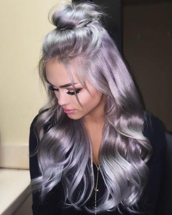 Chica con el cabello brilloso color gris lavanda o lavender gray, largo y ondulado con bun alto