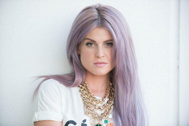 Cantante y presentadora Kelly Osbourne, chica de ojos verde con cabello largo y lacio, color gris lavanda o lavender gray en tonalidad rosa, con collar de cadena dorado