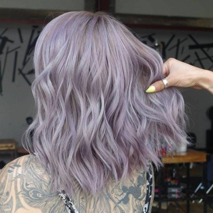 Chica con tatuajes en la espalda y cabello corto a los hombros y ondulado, color gris lavanda o lavender gray