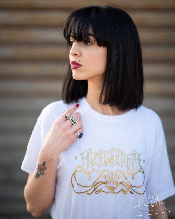 Chica con lunar arriba del labio y tatuaje en el brazo, bob recto corto con fleco en tono negro inky black