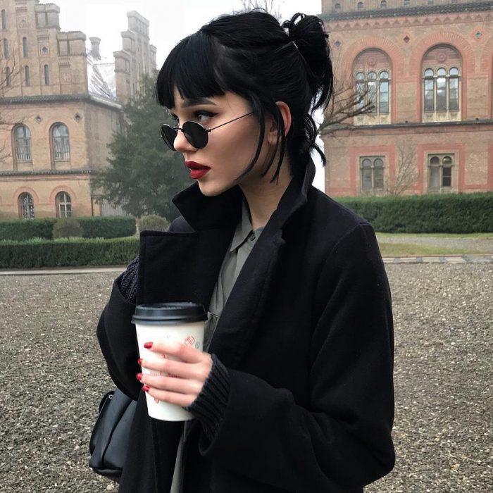 Chica con cabello negro oscuro tono inky black corto con fleco, lentes oscuros bebiendo café
