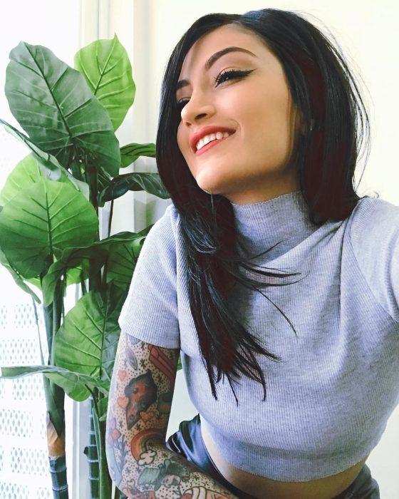 Matu Garcés. chica sonriendo frente a una maceta, tiene cabello negro oscuro tono inky black largo y lacio y tatuajes de arcoíris en los brazos