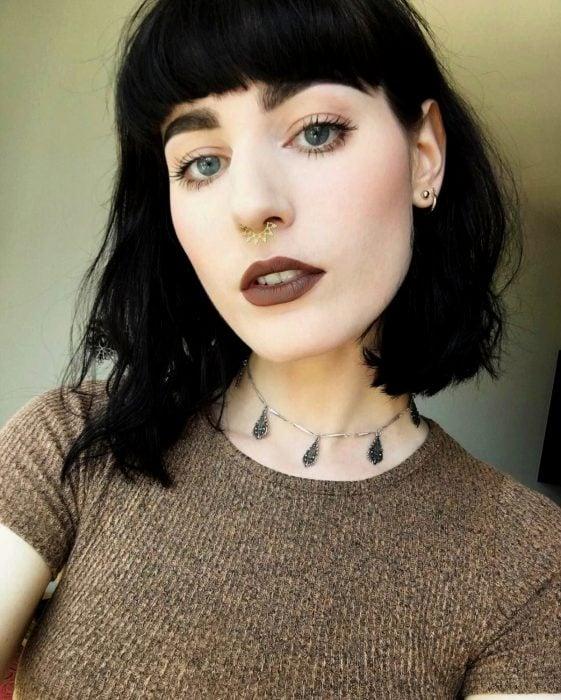 Chica pálida de ojos grises y perforación septum, labial oscuro y cabello corto con fleco color negro oscuro tono inky black