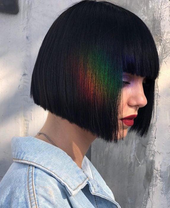 Chica con cabello corto a la barbilla, con fleco, color negro oscuro tono inky black con tinte fantasía color arcoíris