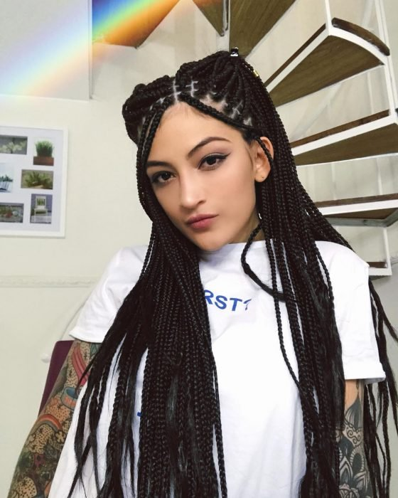 Matu Garcés, mujer de piel morena con los brazos tatuados, trenzas largas en todo el cabello tipo rastas, cabellera negra tonno inky black