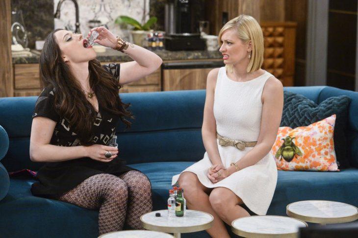 Actrices de 2 broke girls, Kat Dennings como Max Black, y Beth Behrs como Caroline Channing, dos amigas sentadas en un sillón azul bebiendo shots