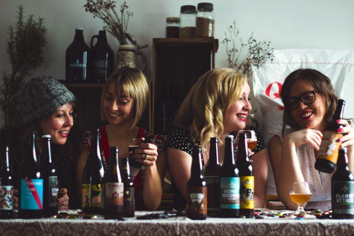 Grupo de cuatro amigas sentadas en una mesa bebiendo cerveza artesanal
