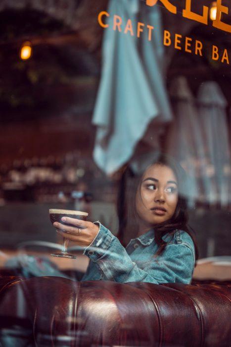 Chica de cabello castaño y chaqueta denim, sentada en una cafetería bebiendo una copa con cerveza