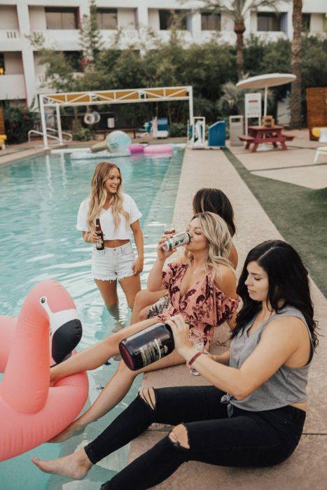 Grupo de cuatro amigas bebiendo cerveza en la alberca