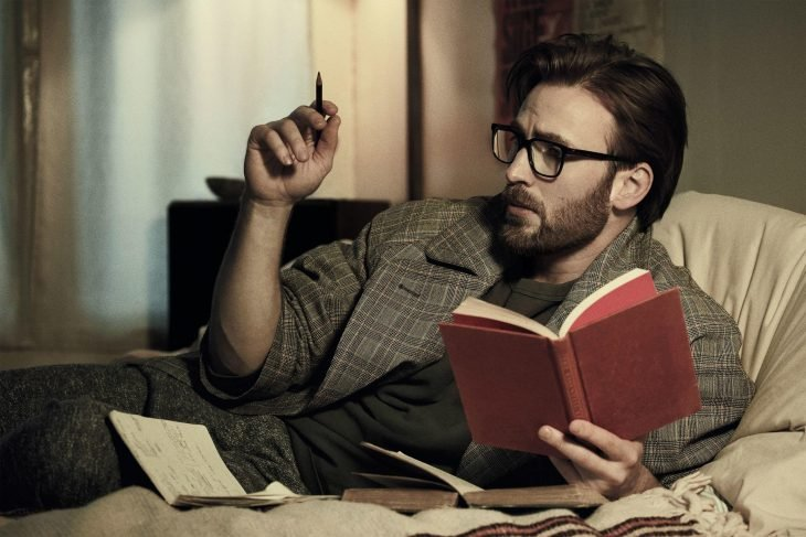 Chris Evans lying on a bed with books around them reading and writing notes