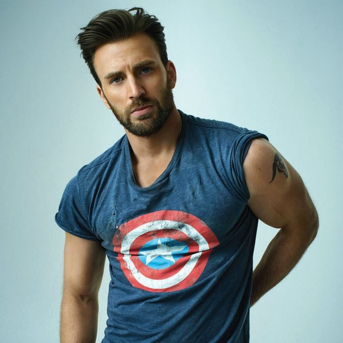Chris Evans posing in a photo shoot with a T-shirt that has the Captain America shield