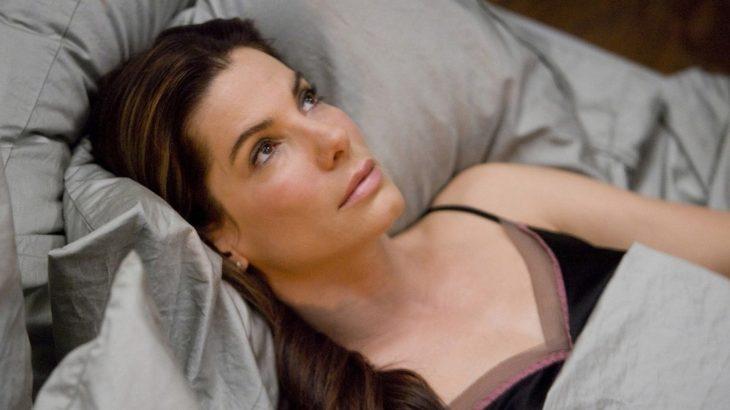 La actriz Sandra Bullock acostada sobre una cama en la cinta La Propuesta